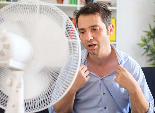 Man sweating infront of a fan - sweat cools us down because it takes energy to turn a liquid to a gas
